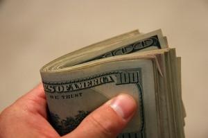 A hand holding hundred dollar bills