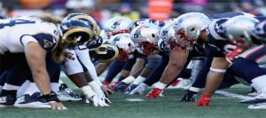 A picture of the New England Patriots and the LA Rams on the field.